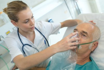 adult male patient in the hospital with oxygen mask